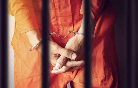 a prisoner hands in handcuffs behind the bars of a prison in orange jumpsuit clothes