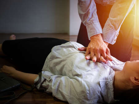 volunteer office man use hand pump on chest for first aid emergency CPR on heart attack woman unconscious, try to resuscitation patient woman at work Imagens