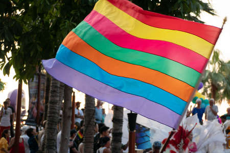 waving rainbow of gay flag and crowd of people in Pride Rainbow Festival Parade. LGBT rights concept