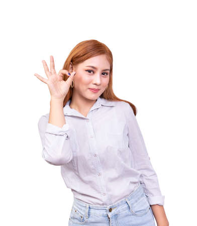 cheerful Asian woman looking at the camera with happy expression. showing OK sign, body language for good emotion. isolated on white background with clipping path, studio shot Stock Photo