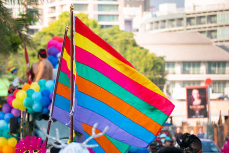 LGBT pride month background. a spectator waves a gay rainbow flag at LGBT gay pride parade festival in Thailand