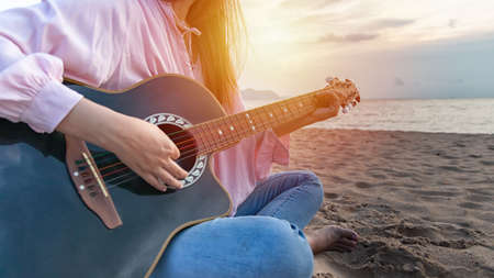 womans hands playing acoustic guitar, capture chords by finger on sandy beach at sunset time. playing music concept
