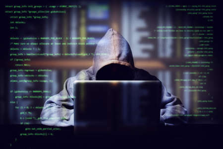 hacker working on a computer code with laptop, double exposure with digital interface around at background. internet crime , hacking and malware concept. anonymous face