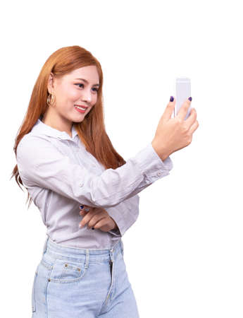 Asian woman using mobile smartphone for selfie ,video chat , face time or video call with smiling face. studio shot isolated on white background with clipping path