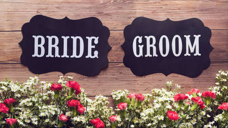 Bride and Groom text sign on wooden background decorated with flower, vintage style. wedding sign concept 免版税图像