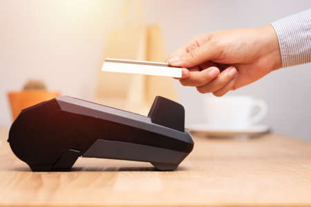 Hand des Kunden mit Kreditkarte für die Zahlung am Point-of-Sale-Terminal im Laden während der Einkaufszeit, bargeldlose Technologie und Kreditkartenzahlungskonzept
