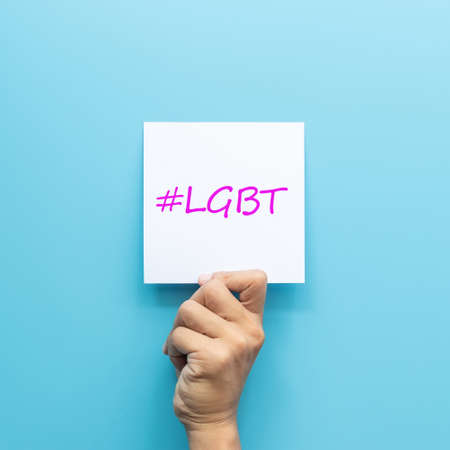 hashtag #LGBT on white paper in hand isolated on blue background