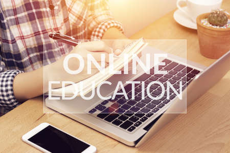 online learning course concept. student using computer laptop for training online and writing lecture note in notebook with text online education on top layer. distance education