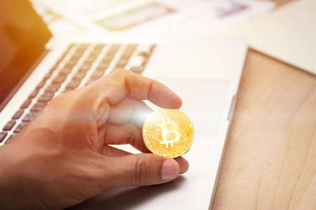 businessman holding cryptocurrency golden bitcoin coin in hand with computer laptop at background. crypto currency, electronic virtual money for web banking and international network payment 写真素材
