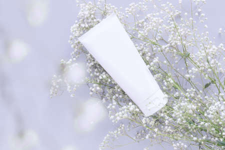 cosmetic nature organic skincare concept. whitening cosmetic in white tube container with blank label for branding packaging mock up, decorate with white flower with copy space 写真素材