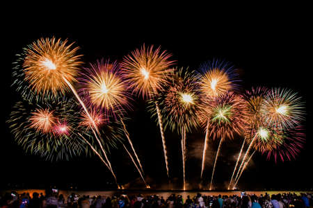 cheering crowd watching colorful fireworks and celebrating on the beach during festival