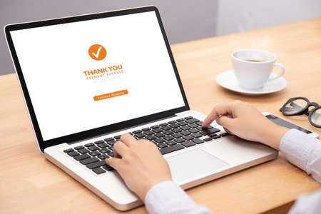 people make transaction payment for shopping online via website on laptop computer with screen payment successful. shopping online and e-commerce concept 写真素材