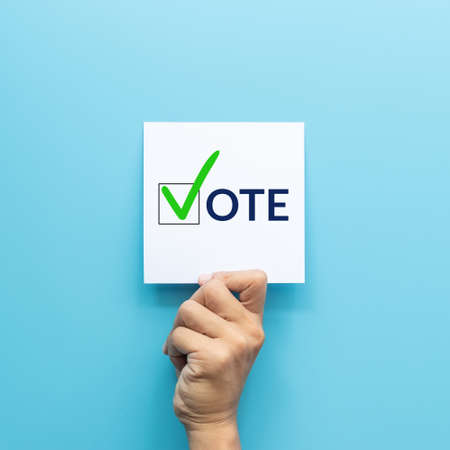 hand holding white paper with the vote and green check mark voting symbols in checkbox of the inscription isolated on blue background
