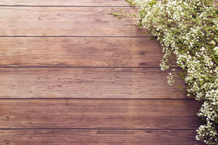 flat lay of garden spring white tiny flowers on wooden plank table background with copy space, retro color style