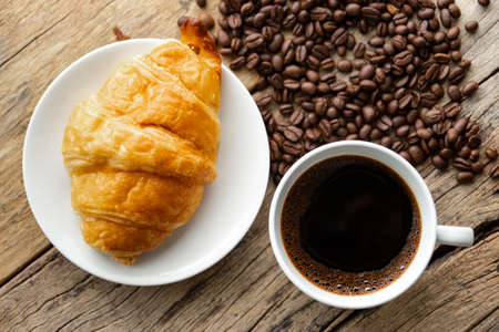 continental breakfast with fresh croissant and hot coffee on wooden background, decoration with coffee bean 写真素材