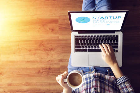 top view of people working on notebook laptop computer from home on wooden floor with startup business and rocket logo on screen, start up ideas business development