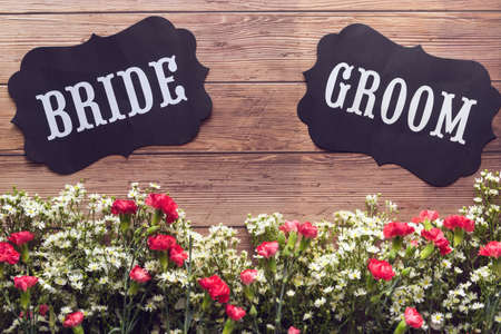 Bride and Groom text sign on wooden background decorated with flower, vintage style. wedding invitation and greeting card
