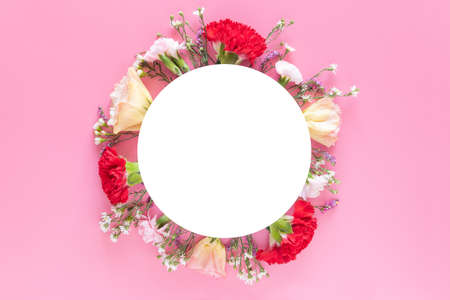 creative layout made with fresh colorful spring flowers on bright pink background with white circle banner label. wedding invitation, posters or greeting design