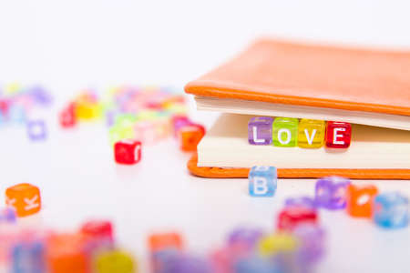 LOVE word on colorful bead block as bookmark in book. love and romantic fiction, happy valentines day greeting card and gift