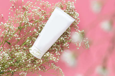 cosmetic nature organic skincare concept. white cosmetic tube container with blank label for branding packaging  mock up, decorate with white flower on pink background with copy space