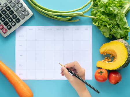 Calories control, meal plan, food diet and weight loss concept. top view of hand filling meal plan on blank paper with calculator and vegetable isolated on blue background