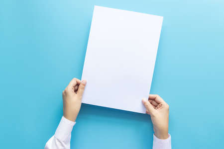 close up hands holding  empty white blank letter paper size A4 for flyer or invitation mock up isolated on a blue background.