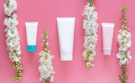 cosmetic nature organic beauty skincare concept. cosmetic tube container with blank label for branding packaging  mock up, decorate with white flower on pink background with copy space 写真素材