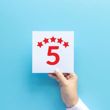 rating and feedback concept. customer holding paper with satisfied review by give five star for service experience 写真素材