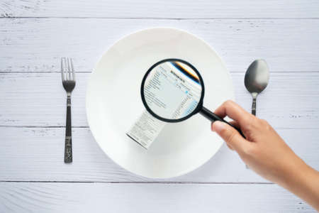 hand use the magnifying glass to zoom in to see the details of the nutrition facts label on the side of the consumer product box on white dish Reklamní fotografie