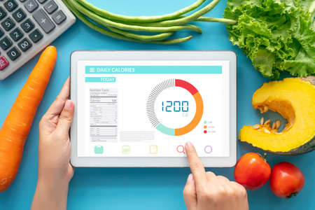 Calories counting , diet , food control and weight loss concept. woman using Calorie counter application on tablet at dining table with fresh vegetable and calculator