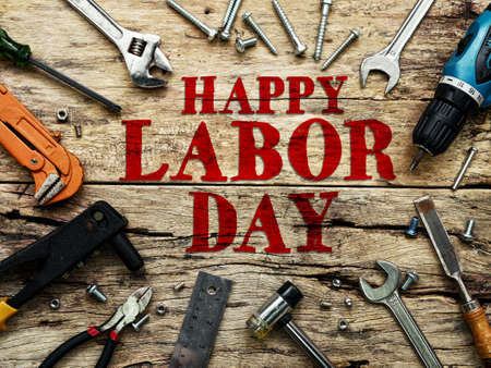 Happy Labor day text in red color on wooden background with construction repair tools. Reklamní fotografie