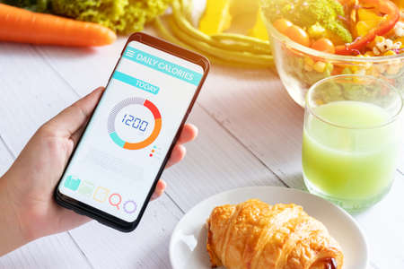 Calories counting and food control concept. woman using Calorie counter application on her smartphone with salad , vegetable, juice and croissant on dining table