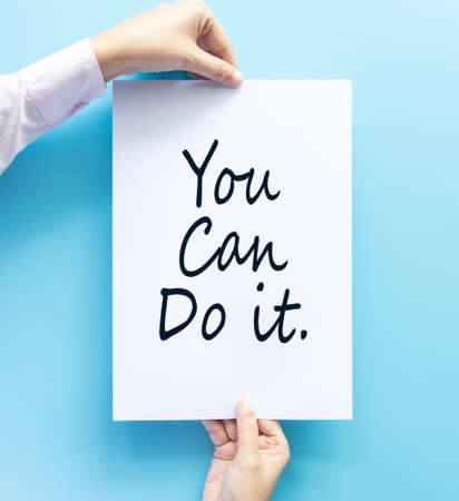 woman hand holding card with the word you can do it isolated on blue background, studio shot. cheer and support quote