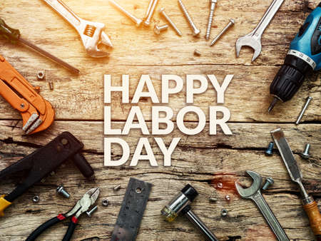 Happy Labor day text in white color on wooden background with construction repair tools. Reklamní fotografie
