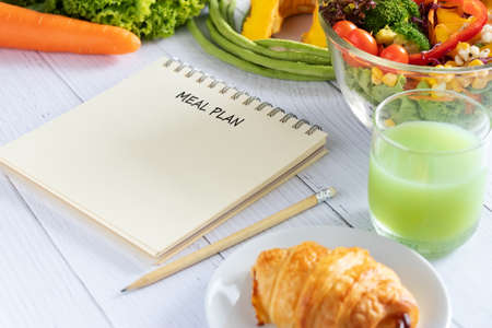 Calories control, meal plan, food diet and weight loss concept. meal plan writing on notebook planner with salad, fruit juice, bread and vegetable on dining table