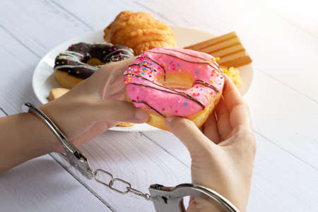 Calories control, food diet and weight loss concept. top view of two hands was control by handcuff, holding doughnut from white dish on dining table