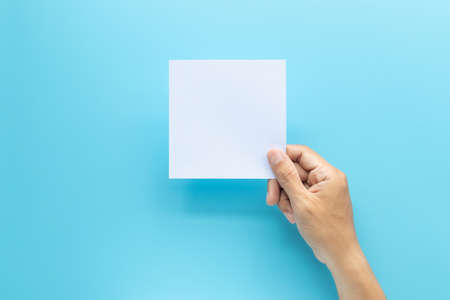 man hand holding blank card paper sheet isolated on blue background with copy space.