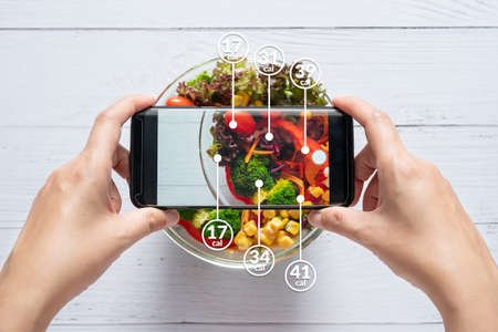 Calories counting and food control concept. woman using application on smartphone for scanning the amount of calories in the food before eat Reklamní fotografie