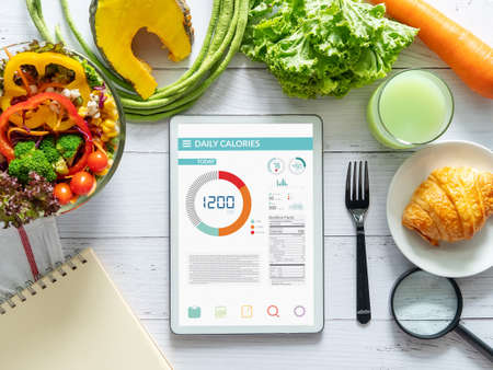 Calories counting , diet , food control and weight loss concept. tablet with Calorie counter application on screen at dining table with salad, fruit juice, bread and vegetable
