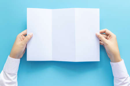 hand holding blank white paper for letter mock up, isolated on blue background with copy space. studio shot, horizontal