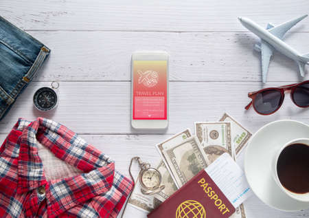 travel plan application technology concept. travel itinerary program list on application on smart phone with travel item accessory, clothes , passport and money on white table Reklamní fotografie