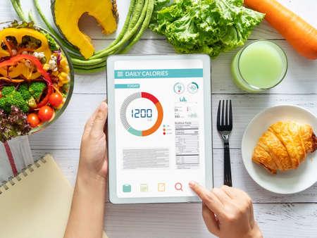 Conteggio delle calorie, dieta, controllo degli alimenti e concetto di perdita di peso. donna che utilizza l'applicazione del contatore di calorie sul tablet al tavolo da pranzo con insalata di verdure fresche Archivio Fotografico