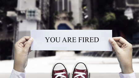 stress business man decide to commit suicide by jump from high building with paper you are fired in hand. dismiss from employment and employee lay off problem