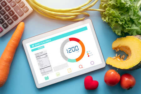 Calories counting , diet , food control and weight loss concept. tablet with Calorie counter application on screen at dining table with vegetable and calculator Banco de Imagens