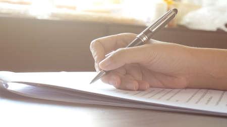 Cerca de manos de mujer firmando o escribiendo un documento en una hoja de papel blanco con bolígrafo negro en la mañana Foto de archivo