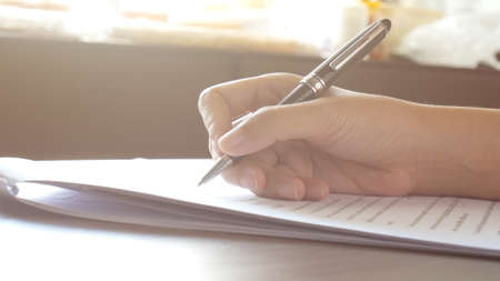 close up of woman hands signing or writing a document on a sheet of white paper with black pen in the morning