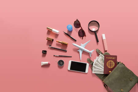 Flat lay of green leather woman shoulder bag open out with cosmetics, accessories , smartphone , money and passport on pink background Banco de Imagens