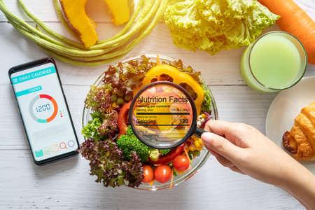concepto de información nutricional. mano use la lupa para acercar y ver los detalles de la información nutricional de los alimentos, ensaladera