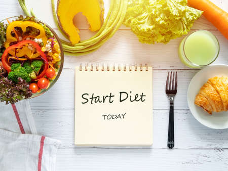 healthy eating, dieting, slimming and weight loss goals concept. target of diet plan on paper with salad bowl, fresh vegetable , fruit juice on dining table