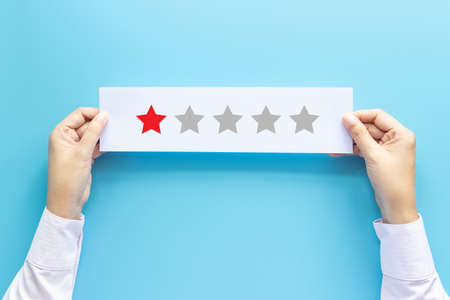 rating and feedback concept. customer holding paper with poor satisfied review by give one star for service experience Banco de Imagens